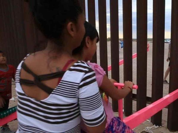 Los niños de la frontera entre México y Estados Unidos juegan en el mismo balancín